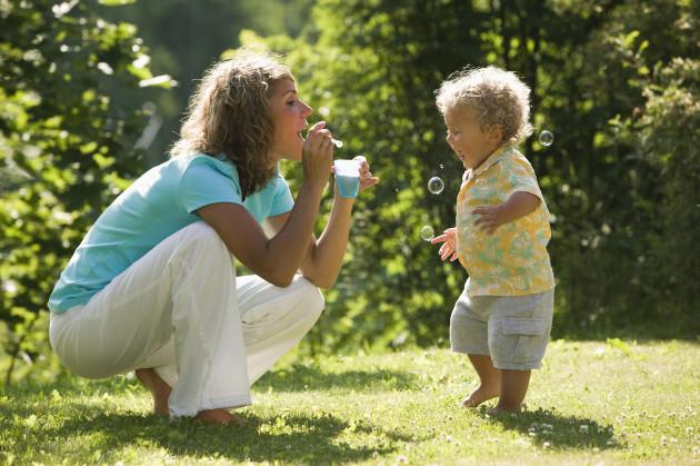 äiti puhaltaa saippuakuplia lapselle