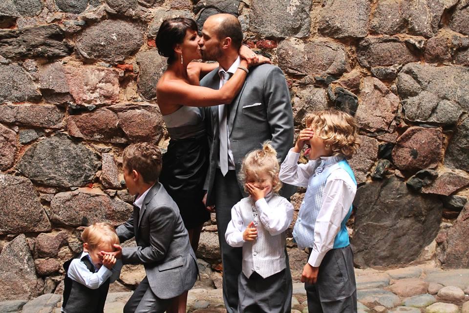 Äiti ja isä pussaa, pojat peittävät silmänsä vieressä.