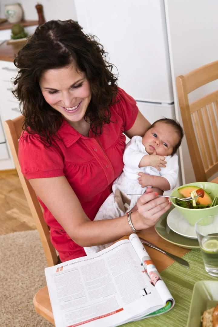 Äiti lukee lehteä ruokapöydässä, vauva sylissä.