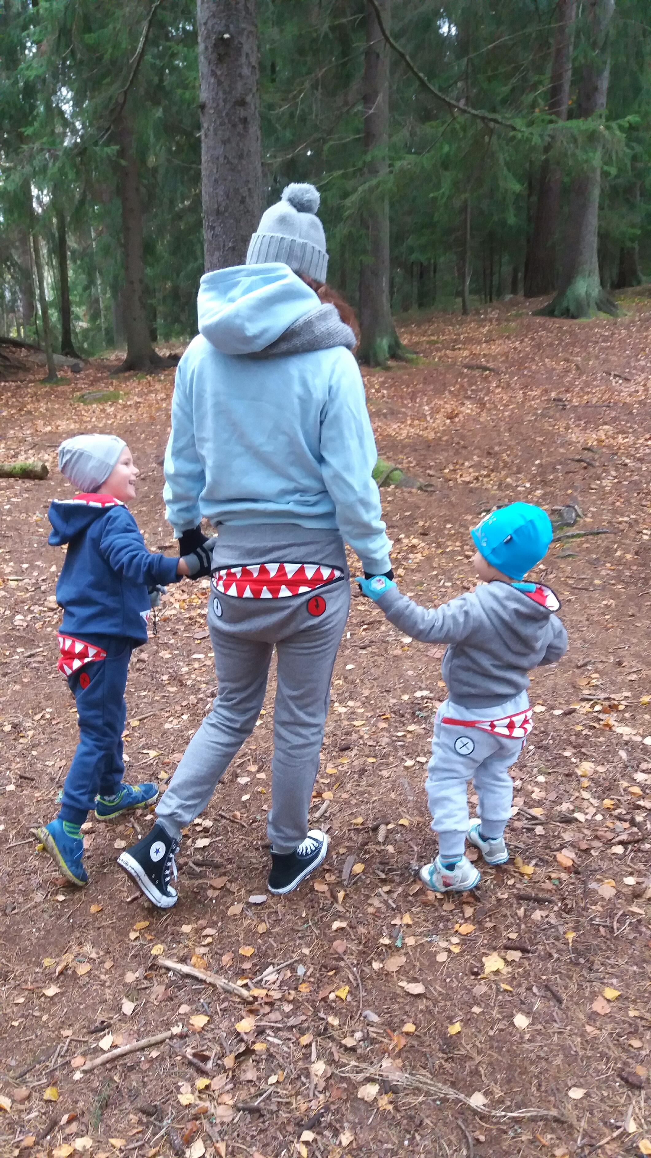 äiti ja pojat kävelevät metsässä