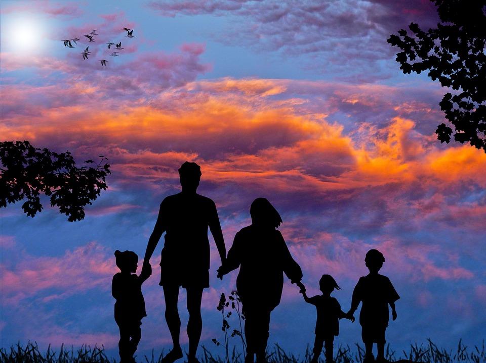 perhe kävelee auringonlaskuun
